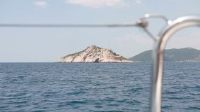 View from the board of the yacht to the island with a fortress stock footage