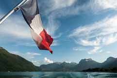 French Flag on the Annecy Lake. View from a boat on the Annecy Lake with the french flag Royalty Free Stock Photo