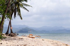View of the boat on the beach with palm trees. In the background of the island. Philippines, the island of Palawan, next to El Nido Royalty Free Stock Photo
