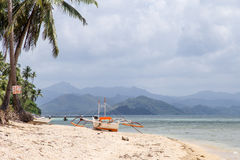 View of the boat on the beach with palm trees. In the background of the island. Philippines, the island of Palawan, next to El Nido Stock Photography