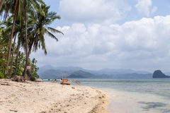 View of the boat on the beach with palm trees. In the background of the island. Philippines, the island of Palawan, next to El Nido Royalty Free Stock Photography