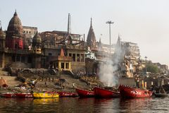 View from a boat glides through water on Ganges river along shore of Varanasi. Royalty Free Stock Photo