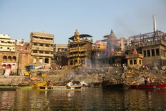 View from a boat glides through water on Ganges river along shore of Varanasi. Stock Photo