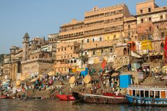 View from a boat glides through water on Ganges river along shore of Varanasi. Royalty Free Stock Image