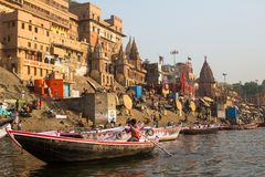 View from a boat glides through water on Ganges river along shore of Varanasi. Royalty Free Stock Photos