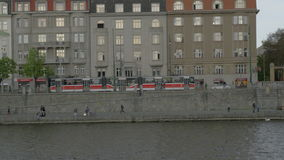 View from boat moving on the Vltava river along Resident Hotel Standard and embankment, Prague, Czech Republic. PRAGUE, CZECH REPUBLIC - APRIL 28, 2016: View stock footage
