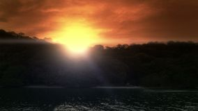 Establishing shot of a tropical island beach at sunset. View from a boat of the sun setting behind a tropical beach paradise stock footage