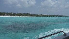 View from a boat on a tropical island with white sand and azure ocean. Maldives stock footage