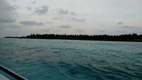 View from a boat on a tropical island with white sand and azure ocean. Maldives 4k stock video footage