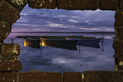 View of boats at sunset. Through a breach in an old brick wall Royalty Free Stock Photos