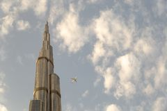 View of a Boing airplane flying close to Burj Khalifa in Dubai stock photography