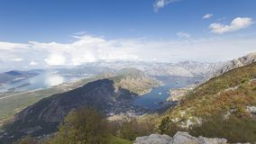 View of the Boka Bay of Kotor. A beautiful view from a high mountain and a bluer sky and white clouds are reflected in the water in the Boka Bay and the sea away Royalty Free Stock Photo