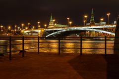 View of Bolshoy Kamenny Bridge and Moscow Kremlin with night illumination on a background of pleasure boats pier royalty free stock images