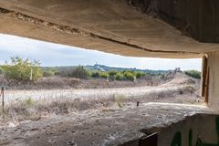 View of the border dividing strip through the embrasure in the concrete security separation fence on the border between Israel and royalty free stock photos
