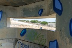 View of the border dividing strip through the embrasure in the concrete security separation fence on the border between Israel and. Lebanon royalty free stock images