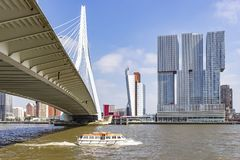 View on the bottom of the Erasmus bridge in Rotterdam where just a passenger boat passes royalty free stock photo