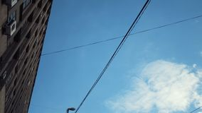 View from the bottom of street lights and tension wires for a trolleybus near the building against a blue cloudy sky stock image