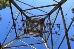 View from the bottom up on a power transmission tower. Against the blue sky stock photography