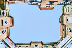 View from the bottom up at the sky, tall old houses, wells, balc Royalty Free Stock Photo