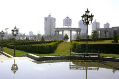 View on the boulevard from the park. Pond, lamppost and  bench. Arch with columns and modern building behind. Ashkhabad. Turkmenistan Royalty Free Stock Photos