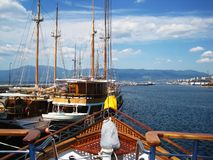 View from bow. On few old sailboats and industrial part of city Rijeka at sunny day Stock Images