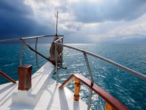 View from the bow of the yacht to the mountain landscape. Sunbeams penetrate the sunset clouds. Concept of summer vacation at sea. For travel agencies. Close up royalty free stock photo