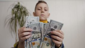 View of boy Counting Many American 100 bills. The little boy counts the American currency. White background, indoor. View of boy Counting Many American 100 bills stock video footage
