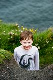 Boy looking up the Cliffs of Moher Tourist Attraction in Ireland Stock Photos