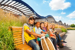 View of boy who holds skateboard and girls near Stock Photos
