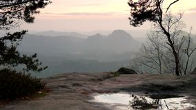 View through branches of trees to deep misty valley within daybreak. Sandstone peaks increased from foggy background. The fog is pink and orange due to sunrise stock video