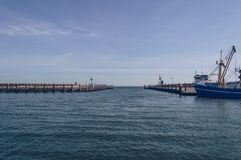 View of breakwater before  open sea. View of breakwater and part of moored fishing trawler in front of open sea in Oudeschild port royalty free stock images