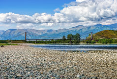 View of the bridge across mountain river with stony shore. View of  bridge across mountain river with stony shore Royalty Free Stock Images
