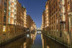 View of the bridge and the brick building in Hamburg, night illumination royalty free stock images