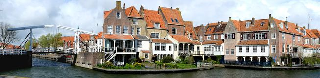 Panoramic view on the bridge in Enkhuizen traditional old brick buildings with tile roofs, Netherlands. View from the bridge in Enkhuizen city in Netherlands Royalty Free Stock Photo