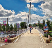 View of the bridge over the river Tammerkoski (Finland, Tampere), with boats on the river and people going over a br royalty free stock photography