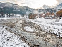 River in Shirakawa, Gifu, Japan. View from bridge over Shirakawa river in early winter season with snow and mountains in background in Gifu, Japan Royalty Free Stock Images