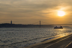 View of the bridge over the Tagus River in Lisbon, at sunset Royalty Free Stock Photography
