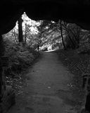 View through bridge underpass of woman walking on forest path. In black and white Stock Images