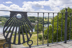 View of the bridge from the village through a fence, Portomarin Royalty Free Stock Image