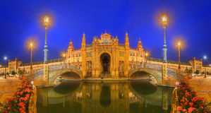 View of bridges and lights in Spain Square at evening, landmark in Renaissance Revival style, Seville, Andalusia, Spain Stock Photos