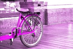View of a bright pink bike with a basket standing on the wooden floor outside.  royalty free stock photo