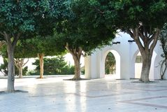 A view of bright white building with arch and green trees in the. Street of small mediterranean town Torremolinos, Andalusia, Spain Stock Photos