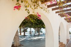 A view of bright white building with arch and pink violet bougai. Nvillea and green trees in the street of small mediterranean town Torremolinos, Andalusia Stock Image