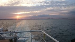 View of the British coast in Dover from a ferry. Sunset over the channel with troubled water Stock Images