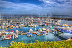 View of Brixham marina harbour walls Devon England UK with calm blue sea and sky in HDR Royalty Free Stock Images