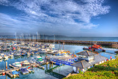 View of Brixham marina harbour walls Devon England UK with calm blue sea and sky in HDR Stock Photo