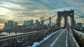 View of Brooklyn Bridge on Winter with Snow and an Amazing white and blue sky royalty free stock image