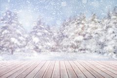 View on a brown wooden table against a winter forest in blur and snowfall royalty free stock photos