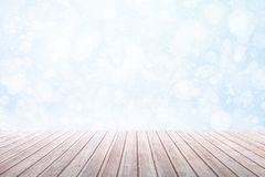 View on a brown wooden table against a winter snowfall with bokeh royalty free illustration