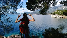 The view of the brunette girl travelling with a rucksack from the back. The girl admires the view. Green area with fir trees Stock Photo